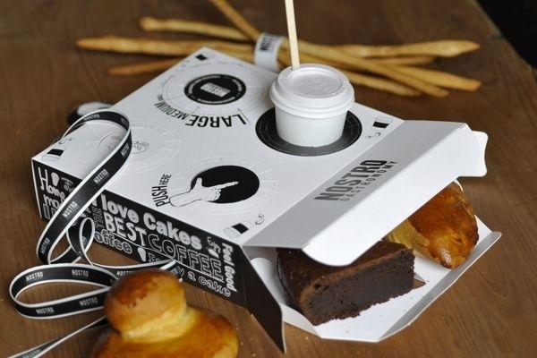 Una caja de pastelería con porta café incorporado