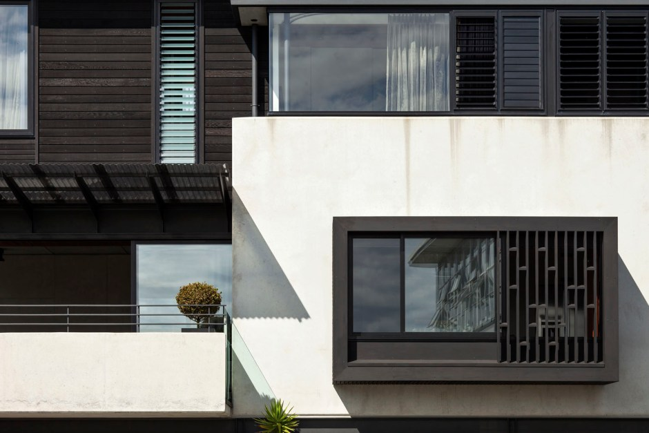 Gerrad Hall townhouse black cedar and pop-out windows soften concrete expanse