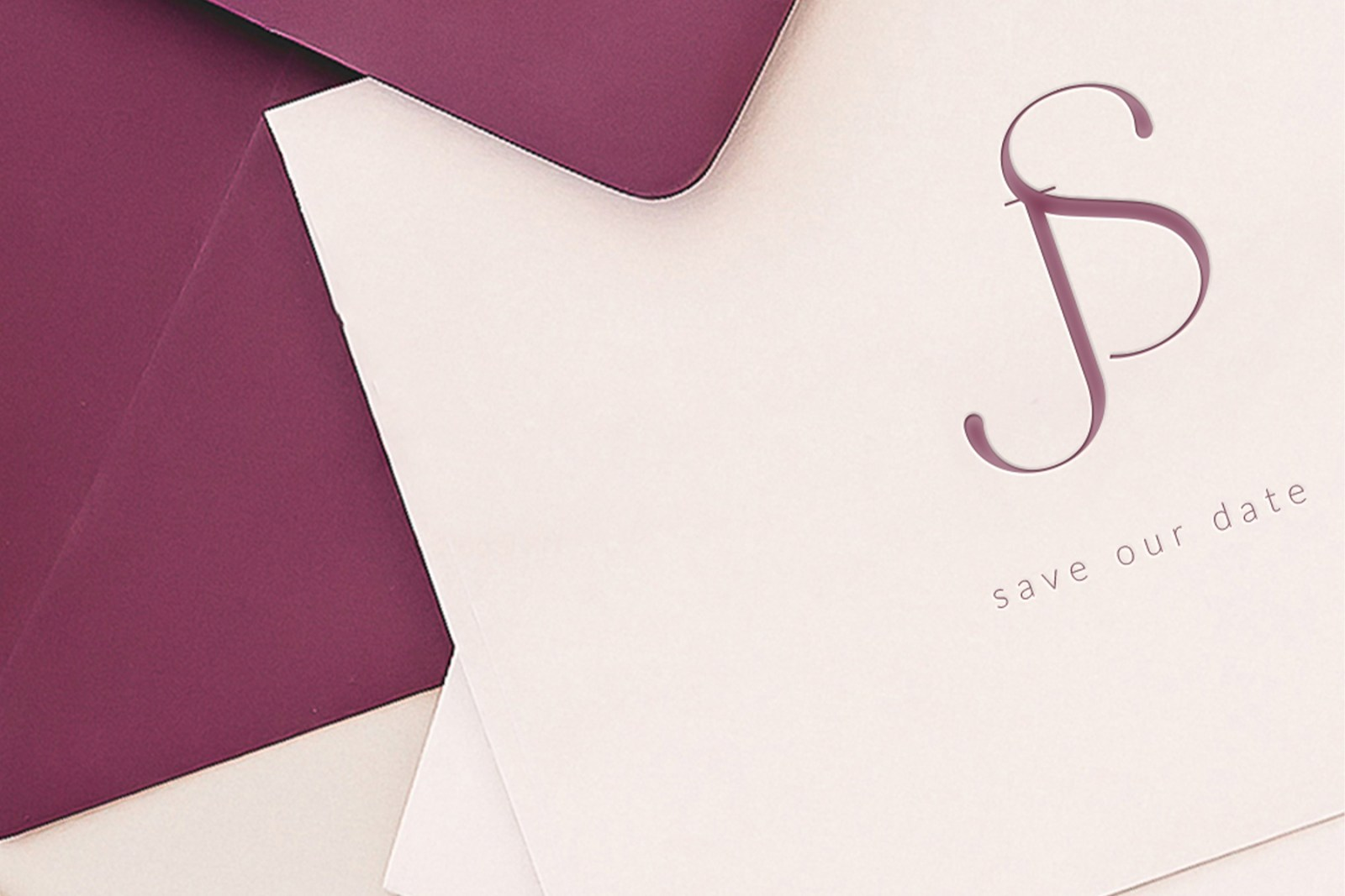modern wedding monogram with bride and groom initials J and S in a modern clean styled sans serif type on blush card letterpress in the foreground backed by a fuchsia colored envelope in the background