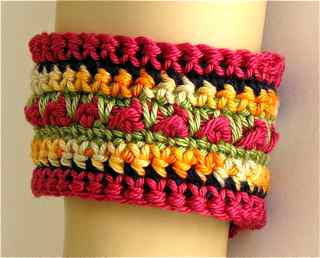 Close up of the single crochet stitch color changes and center accent aran stitch texture of bracelet cuff.