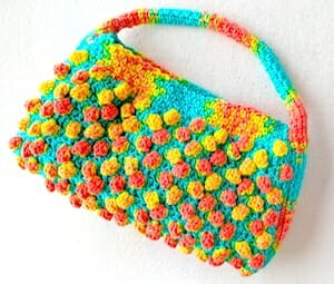 "One ball of hand painted yarn, its colors intentionally ""pooled"" into two stitch patterns (popcorns and seed/moss/linen st) to create this ""Florida Peaches Handbag"""