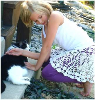 "Tween-aged girl wears an ""exploded doily"" style skirt by Doris Chan as she pets a cat."