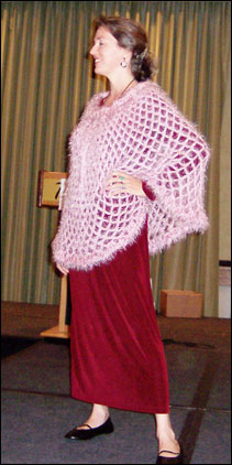 Vashti models a mesh poncho crocheted of a mauve-pink silky angora-like medium weight yarn called Gedifra Micro Chic.