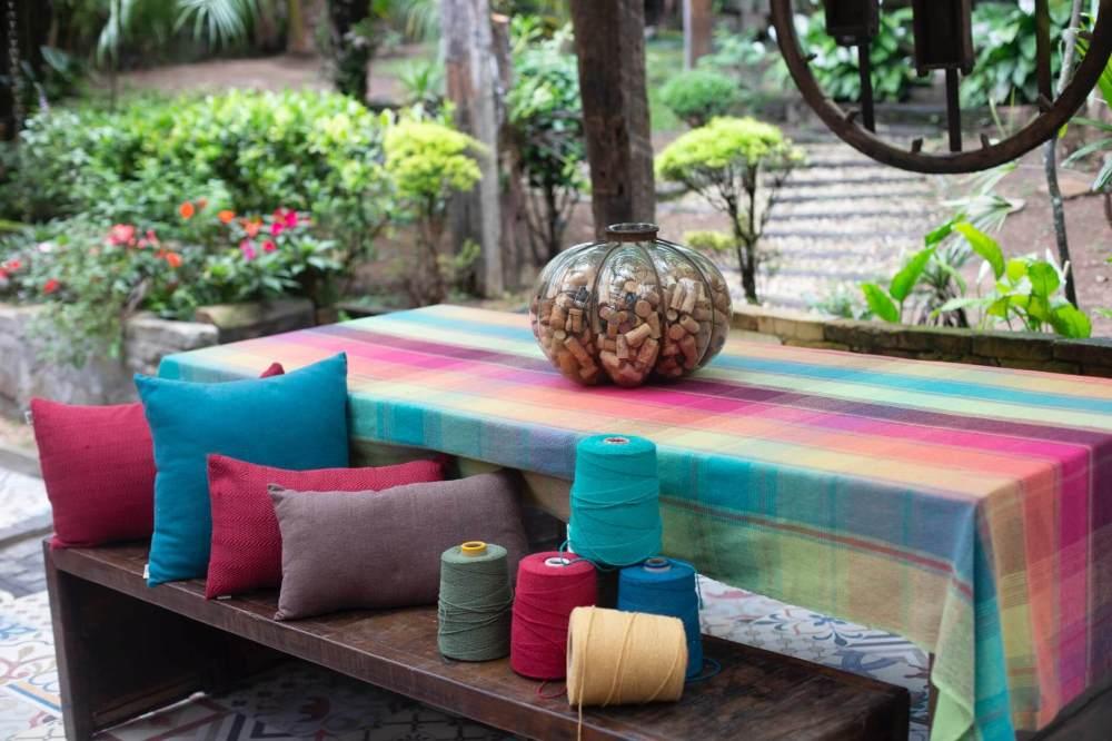thread spool on picnic table beside throw pillow