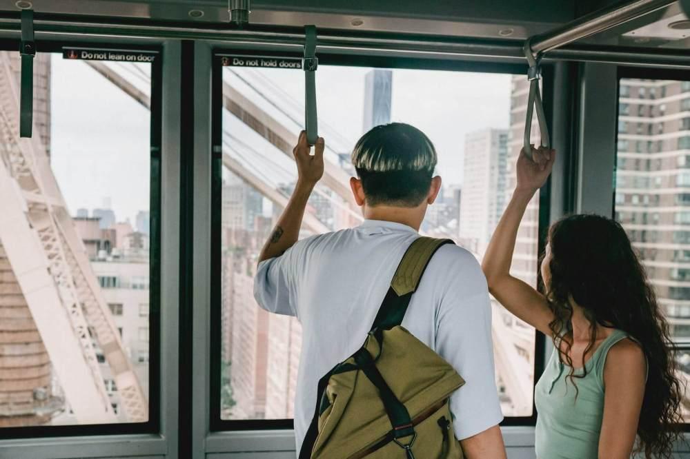 unrecognizable couple riding public train in urban city