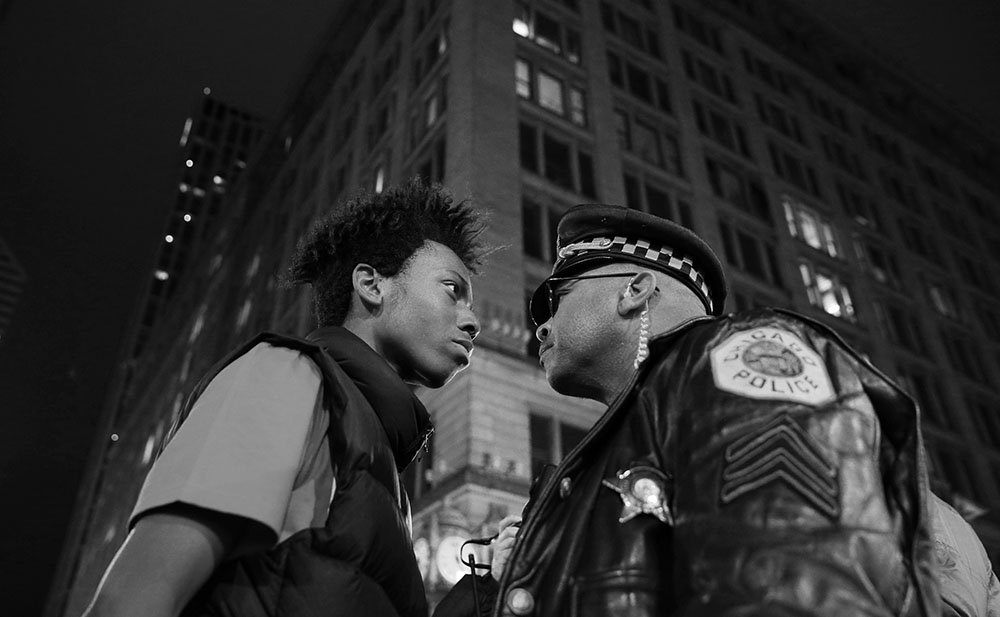 Lamon Reccord, left, scolds a police sergeant during a police violence protest and march at State and Randolph streets Wednesday, Nov. 25, 2015, in Chicago. (John J. Kim/Chicago Tribune)