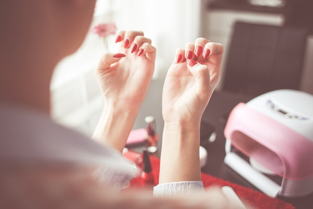 woman looking at her red nails