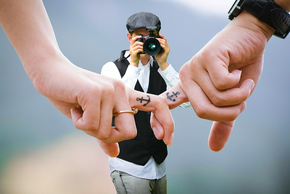 man taking a photo of intertwined fingers with anchor tattoos