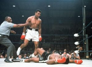 FILE - In this May 25, 1965, file photo, heavyweight champion Muhammad Ali is held back by referee Joe Walcott, left, after Ali knocked out challenger Sonny Liston in the first round of their title fight in Lewiston, Maine. Ali, the magnificent heavyweight champion whose fast fists and irrepressible personality transcended sports and captivated the world, has died according to a statement released by his family Friday, June 3, 2016. He was 74. (AP Photo/File)