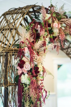 wedding ceremony arch in green, deep red, white and pink by geneva florist