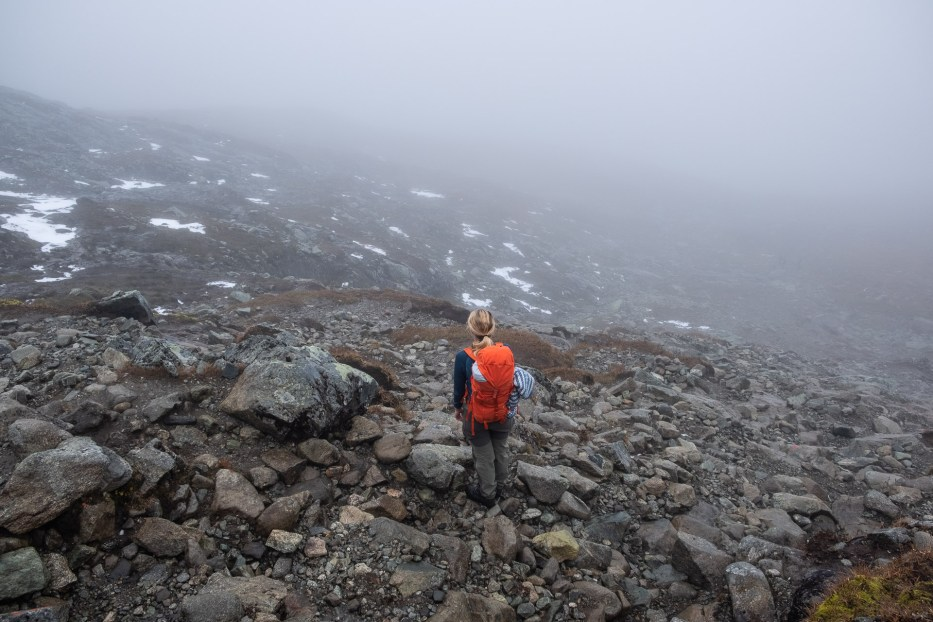 person with orange backpack in a foggy mountain landscape