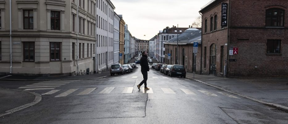 Lone man crossing a road with colourful houses in Oslo Norway