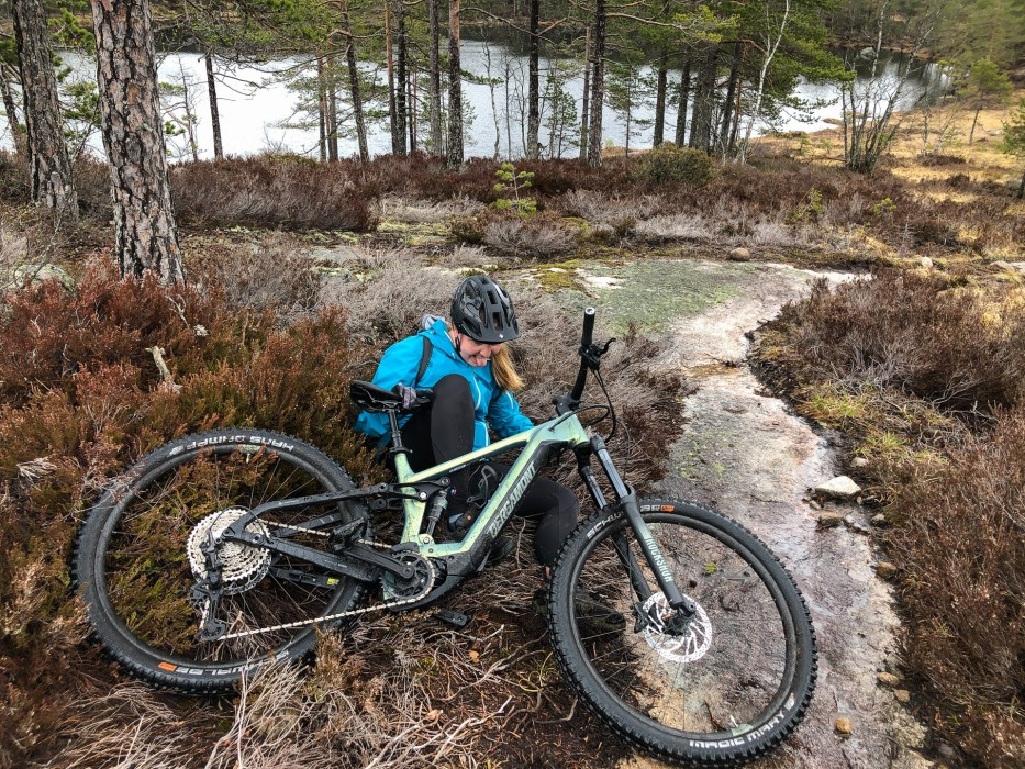 woman underneath a trail bike in a forest