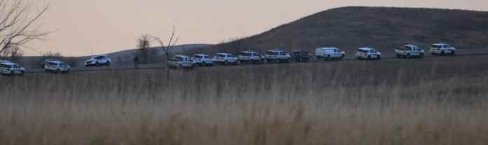 More than a dozen police vehicles line a North Dakota road at sunset