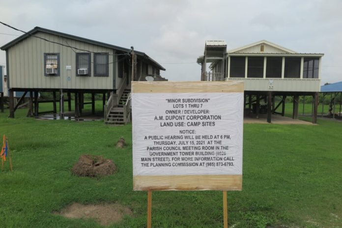 White sign giving notice of A.M. Dupont's proposal to subdivide its parcel of land to enable its sale to fishing camp owners on the Isle de Jean Charles, Louisiana, with two raised houses in the background.