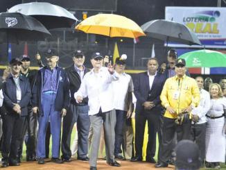 Alejandro Asmar Sánchez (Chito) a quien está dedicado el torneo de béisbol otoño-invernal realiza el lanzamiento de la primera bola en el partido inaugural de la justa celebrado anoche en el estadio Cibao entre las Águilas Cibaeñas y los Gigantes del Cibao