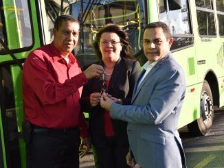 Rafael Ovalles director general del INFOTEP recibe la llave de autobuses de la OMSA de manos de José Oreste Martínez. Observa la subdirectora del INFOTEP Maira Morla