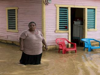 Una mujer camina por una calle inundada hoy, viernes 22 de septiembre de 2017, tras el paso del huracán María en la ciudad de Nagua (República Dominicana). Un total de 38 localidades de República Dominicana siguen aisladas a causa del desbordamiento de ríos, arroyos y cañadas que provocó el huracán María, que aunque se alejó del país, sigue provocando lluvias en algunas zonas del noreste y este del país, informaron hoy fuentes oficiales.