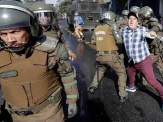 Fuerzas policiales de Chile deteniendo a un manifestante. Protestas por visitas del Papa.