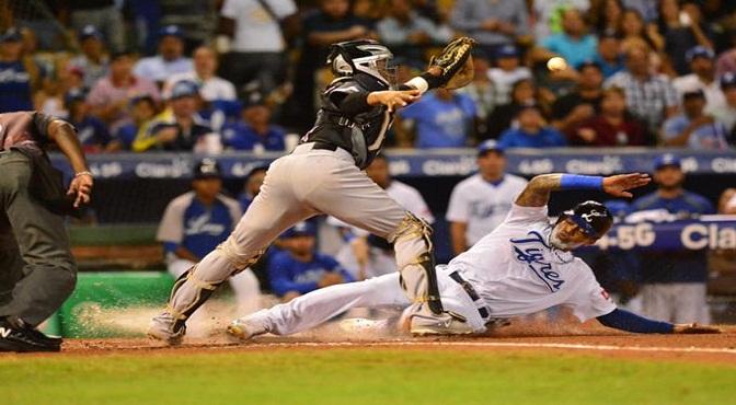 Engel Beltré, del Licey, se barre a salvo en el home plate, mientras que el receptor Carlos Paulino, de los Gigantes, trata infructuosamente de ponerle out.