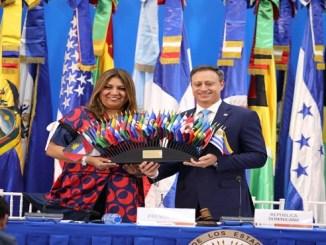 Procurador General Jean Alain Rodríguez recibe las banderas de las Américas de manos de Farah Urrutia Secretaria de Seguridad Multidemsional de la Organización de Estados Americanos (OEA)