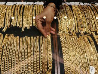 Vendedor colocando cadenas de oro en un mostrador de la joyería VJ Gold and Diamond de Kuala Lumpur, Malasia.