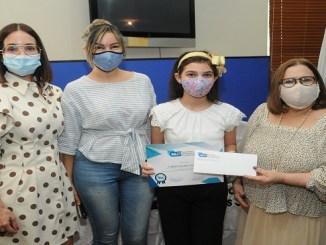 La niña Lizbeth Grullón Fondeur recibe el reconocimiento de manos de Claudine Nova y Mirna Pimentel, acompañada de su madre Elizabeth Fondeur.