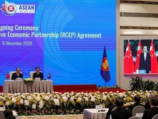 Foto del domingo del primer ministro de Vietnam', Nguyen Xuan Phuc (I) junto al ministro de Industria y Comercio Tran Tuan Anh viendo por una pantalla al ministro de Comercio de China Zhong Shan (D) y al primer ministro Li Keqiang firmando el documento de fundación del RCEP durante una cumbre en Hanoi.