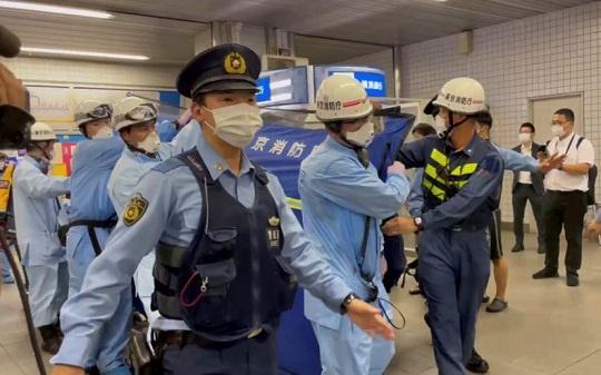 Trabajadores de rescate llevan a una de las personas heridas en un ataque con cuchillo en un tren en Tokio, este viernes 6 de agosto.