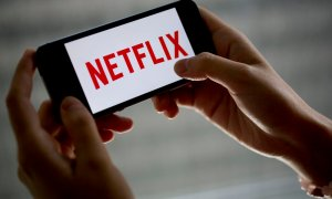 """The Netflix Inc. is displayed on an Apple Inc. iPhone 5s in this arranged photograph in Washington, D.C., U.S., on Wednesday, July 9, 2014. """"House of Cards,"""" and """"Orange Is the New Black,"""" two Netflix Inc. series that have boosted the popularity of online viewing, will compete for television's top honors as nominees for Emmy awards in drama and comedy. Photographer: Andrew Harrer/Bloomberg via Getty Images"""