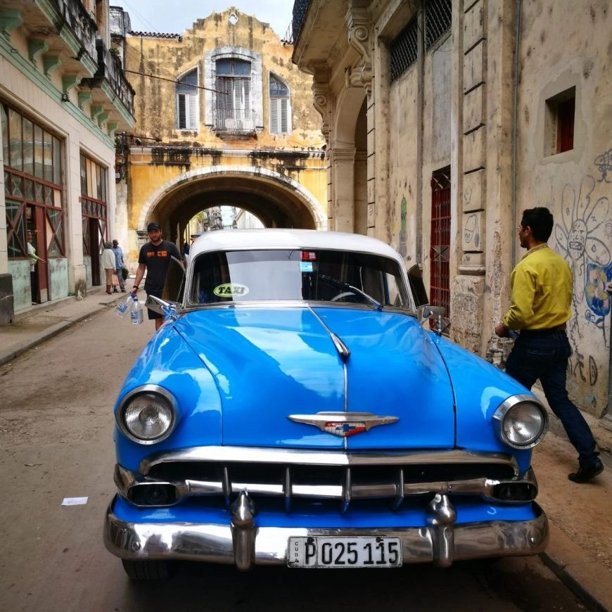 Classic old car parked in crumbling old street in old Havana