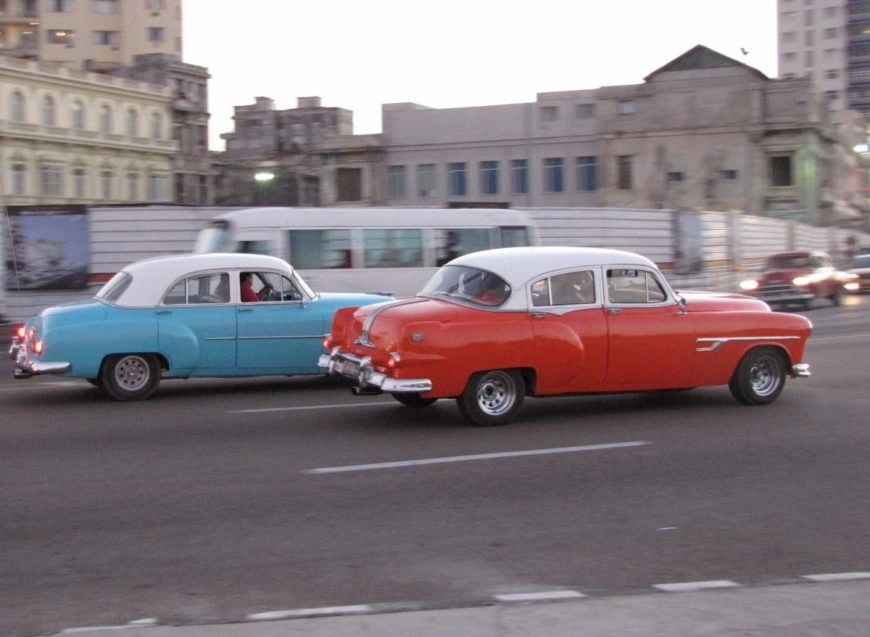 Classic American cars whizzing past at sunset along the Malecón, Havana