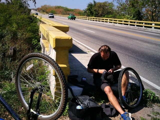 Destination Addict - Fixing puncture number 1 of our solo cycle tour, just outside of Havana, Cuba