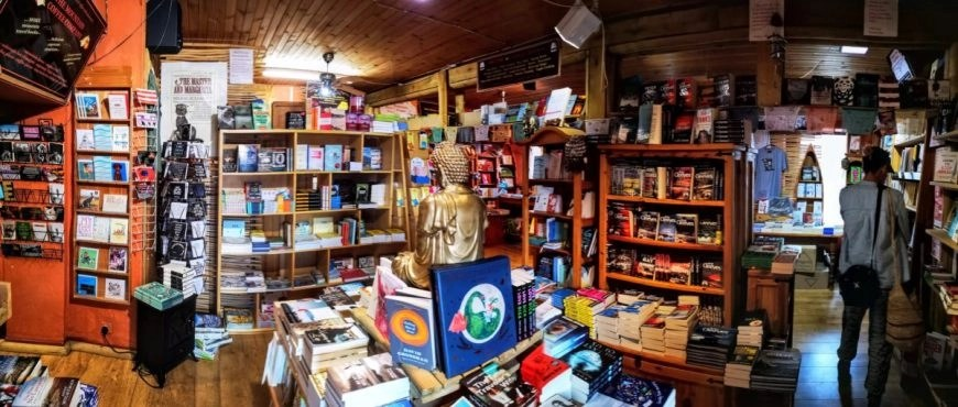 Browsing the beautiful book collection at Mountain Coffee Company, NC500 – An Epic Itinerary For Scotland's North Coast - Destination Addict