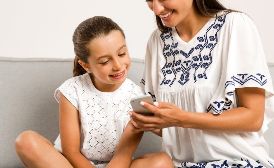Mom teaching child to use the phone