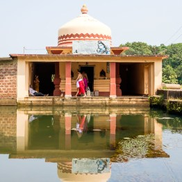 Small temple next to water in Goa
