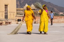 Women dressed in yellow sari cleaning the floor