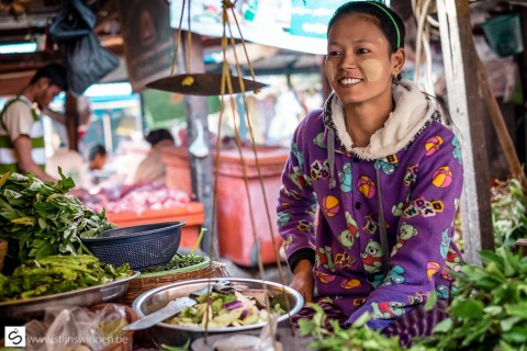 Young woman on market with thanaka on face