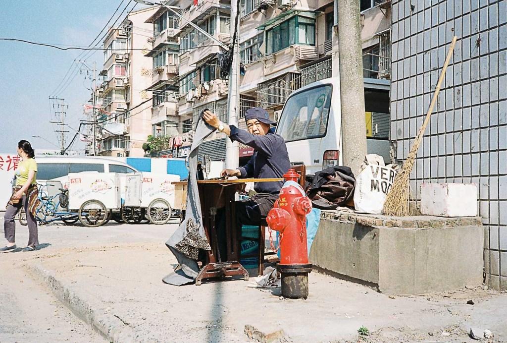 Homem costurando nas ruas de Xangai