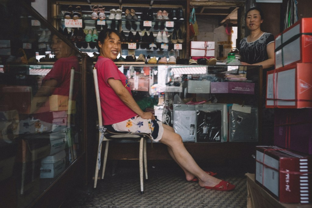 Compras no mercado de Yiwu Mulher sentada em cadeira dentro de loja de sapatos na China