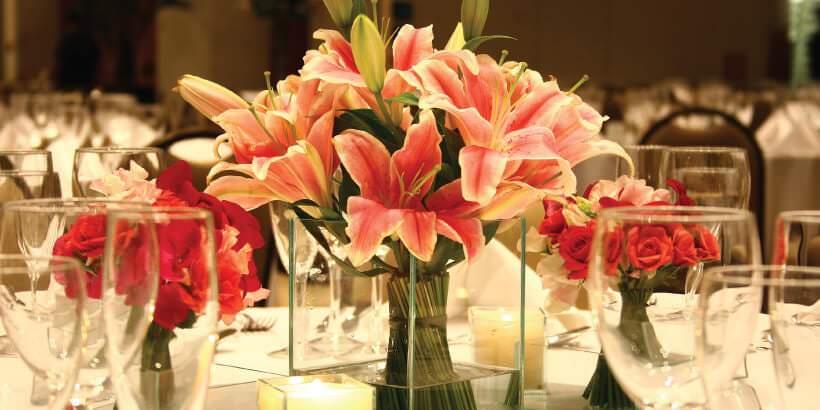3 Dicas para quem deseja investir em flores artificiais Mesa de restaurante com arranjo de flores artificias em vaso transparente