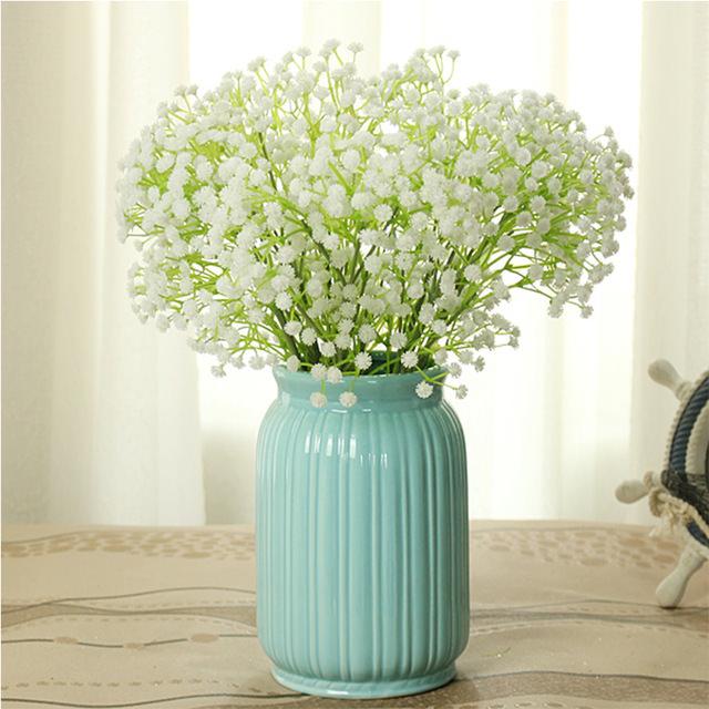3 Dicas para quem deseja investir em flores artificiais Vaso de cerâmica azul com delicadas flores artificiais brancas