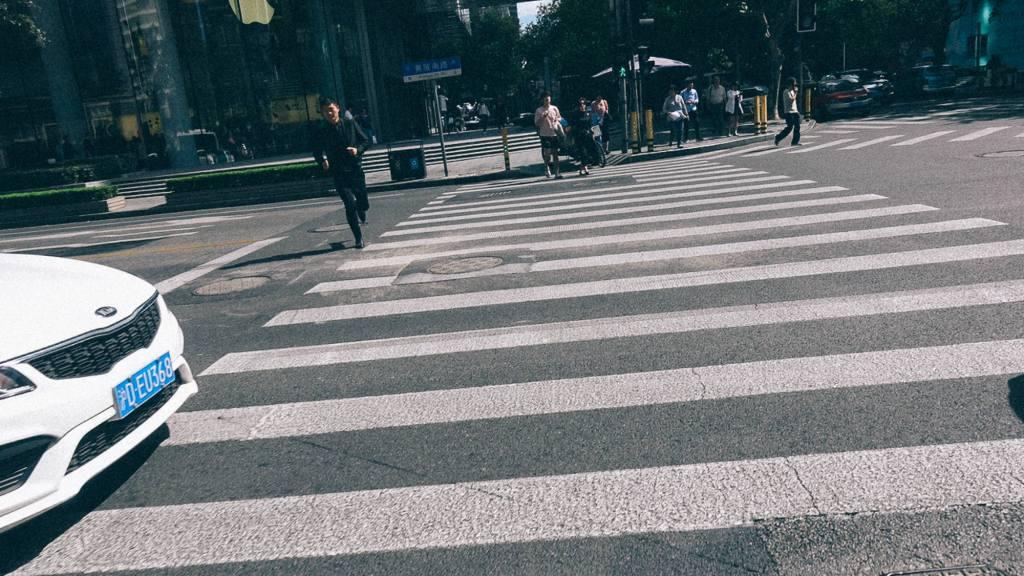 3 destinos para uma importadora Pessoa atravessando faixa de pedestre em rua movimentada na China