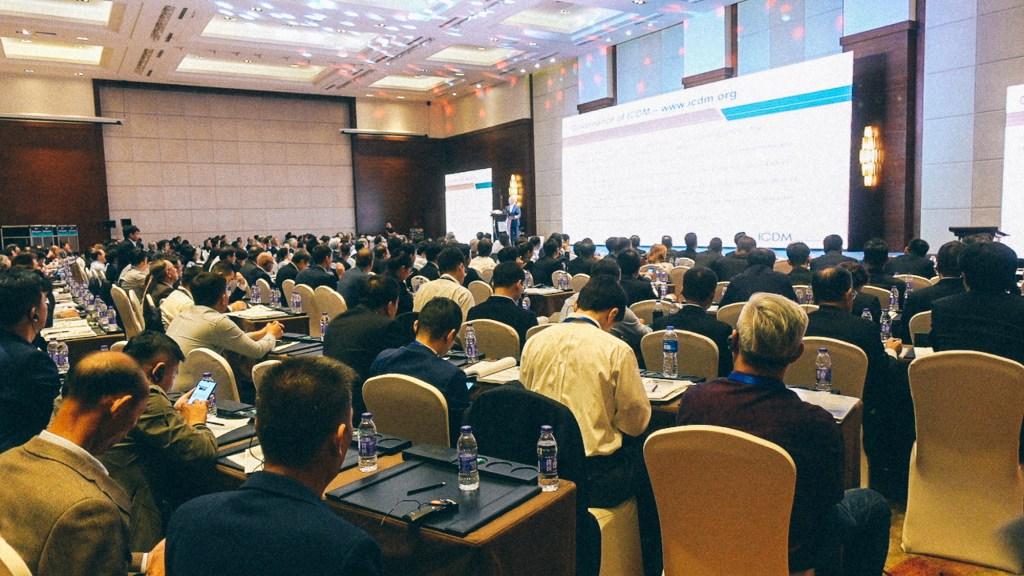Como importar variedade no mercado de Yiwu Pessoas assistindo palestra em auditório em estabelecimento fechado