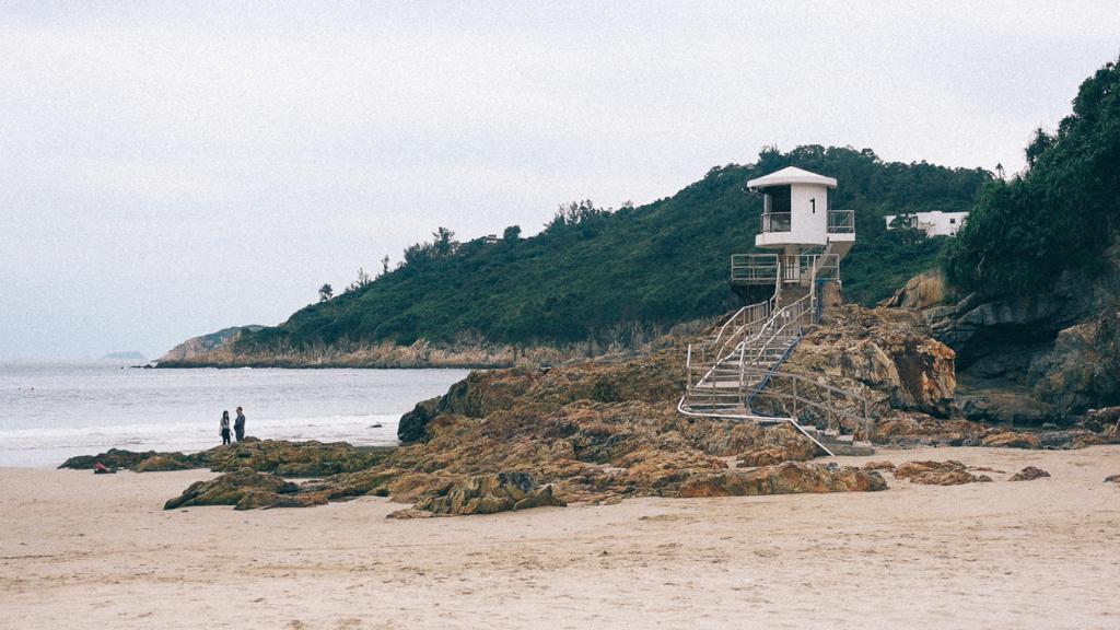 Como importar da China em grande quantidade Praia de Big Wave Bay com surfistas