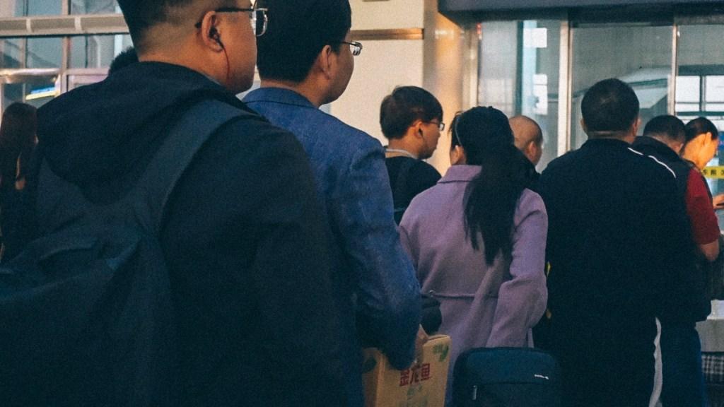 O que comprar no vietnã Fila de pessoas no vietnam esperando para entrar em fábricas