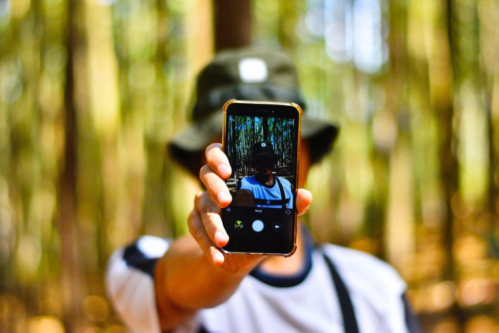Xiaomi no Brasil Homem com celular Xiaomi em meio trilha