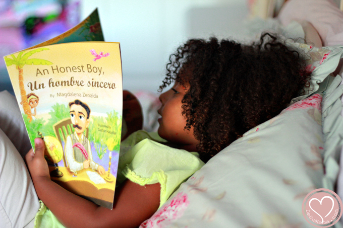 biracial baby girl reading hispanic heritage month childrens book on cuban legand jose marti