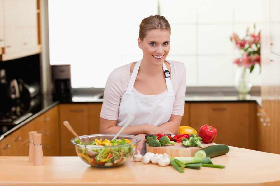 mujer en la cocina con vegetales para ser vegano