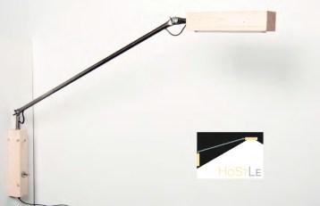 """Eine Leuchte aus Holz und Stahl, deren Bestandteile durch Form und Materialität die beteiligten Werkstätten der Lebenshilfe Detmold e.V. repräsentieren. Die simple Mechanik und schlichte Formsprache von """"HoStLe"""" suggeriert Werkstattcharakter mit einer ehrlichen reduzierten Optik."""